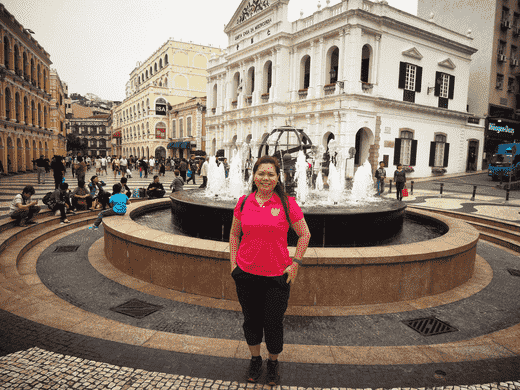 Travel blogger in front of the fountain at Largo do Senado in Macau