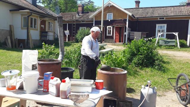 Mies keittää punamultaa vanhassa pihapiirissä.