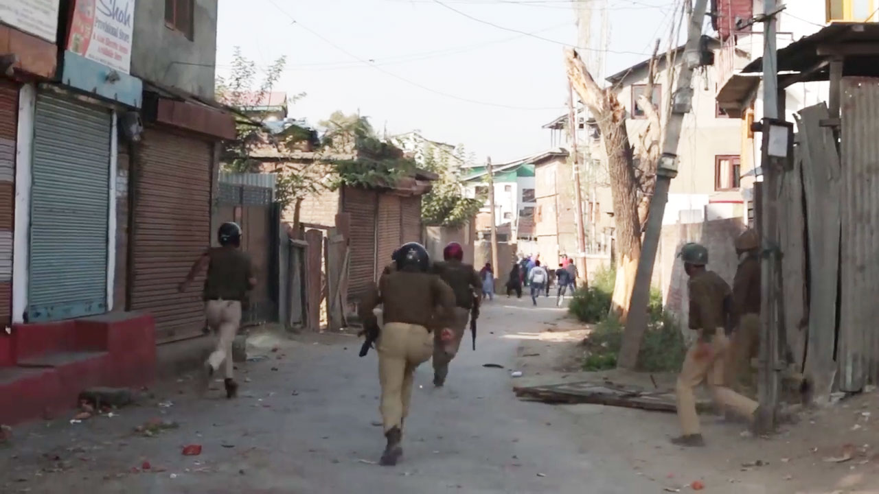 Security forces chase away protestors during a protest demonstration in Srinagar