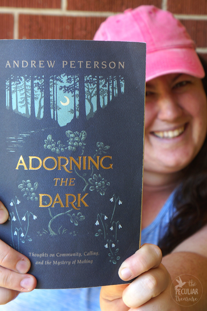Woman holding the book Adorning the Dark by Andrew Peterson