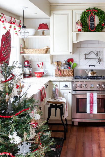 Farmhouse style kitchen with red accents and boxwood wreaths as Christmas decor