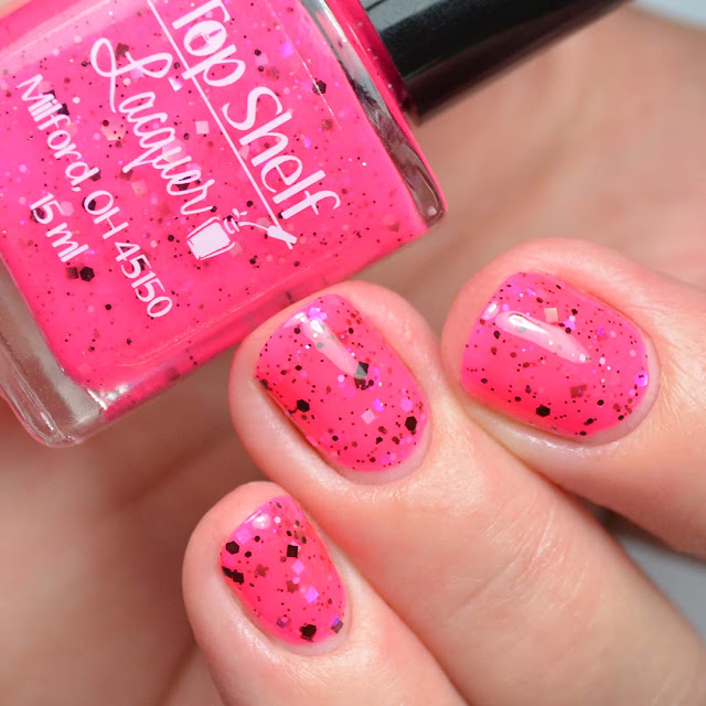 hot pink nail polish with black and iridescent glitter swatch