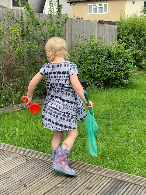 Toddler in the garden with a net in one hand and a spade in the other
