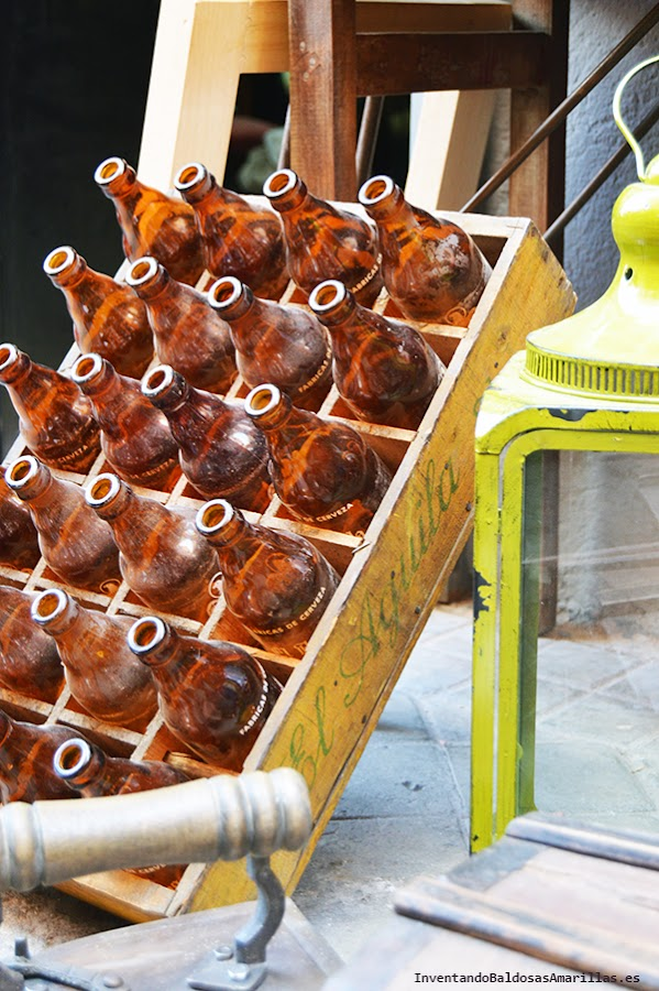Caja de madera con botellas de cristal.