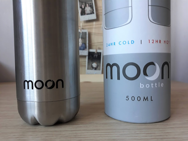 The image shows a stainless steel reusable water bottle standing next to it's white cardboard tube. It shows the bottom of the bottle & tube, revealing the moon bottle logo