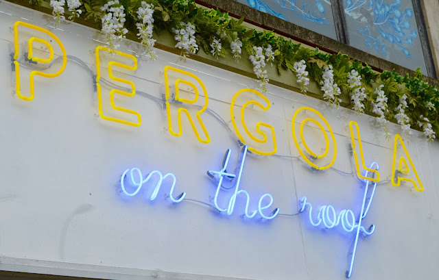 Pergola on the Roof neon sign and flowers