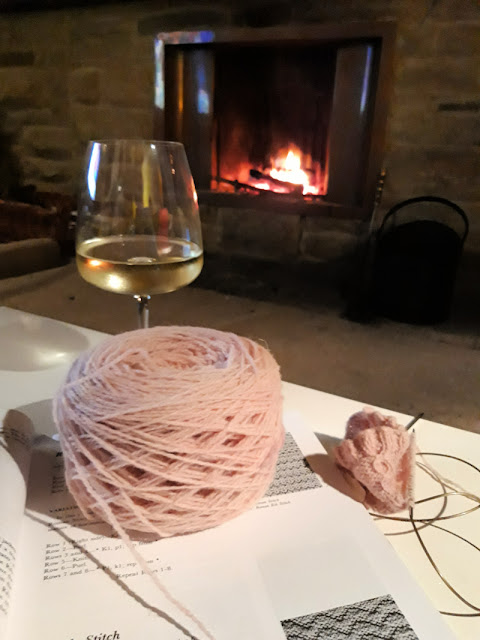 A coffee table with an open stitch dictionary and a glass of white wine on it.  A cake of pink yarn and some knitting are sitting on the book, and in the background is an open fire