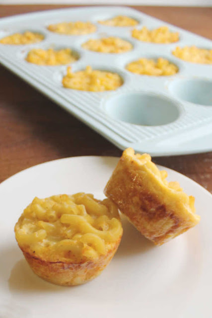 two servings of mac and cheese on plate with cupcake tin filled with more in background
