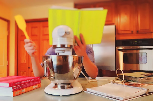 Busy mom in the kitchen with cookbooks and mixer