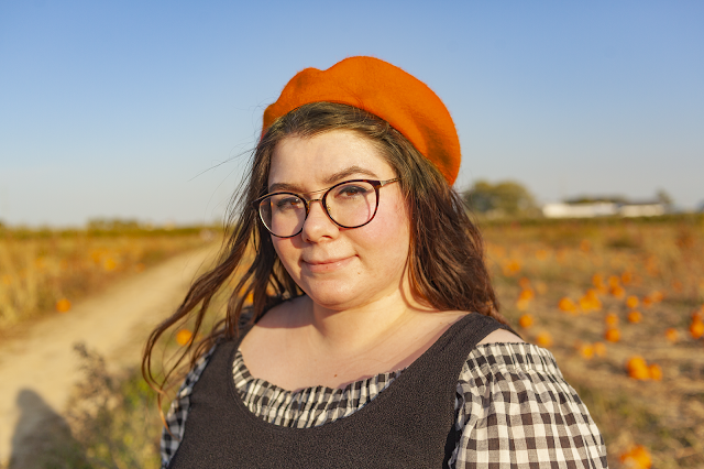 An portrait consisting of a brunette women with a burnt orange beret, wearing a black and white gingham off the shoulder blouse under a sleeveless scoopneck black dress under a black pleated midi skirt. Her eyes are squinting from the sun as she faces the camera on a 3/4 angle.