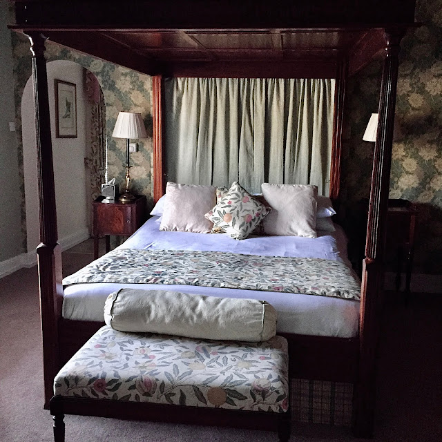 A traditional four poster bed in a hotel room with floral wall paper and upholstery