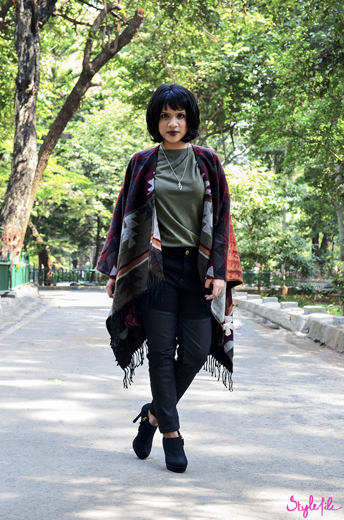 Image of fashion blogger Dayle Pereira wearing a navajo print poncho coat, leather panel black jeans, black booties, plum copper eye makeup and a dark brown lip