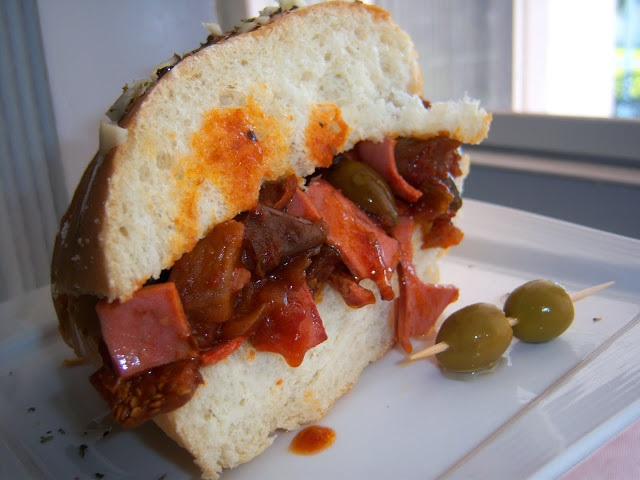 this is a recipe card for fried bologna and eggplant appetizer sandwich with olives and sauce in a hard crusted Italian roll. This is on a dish by a picture window.