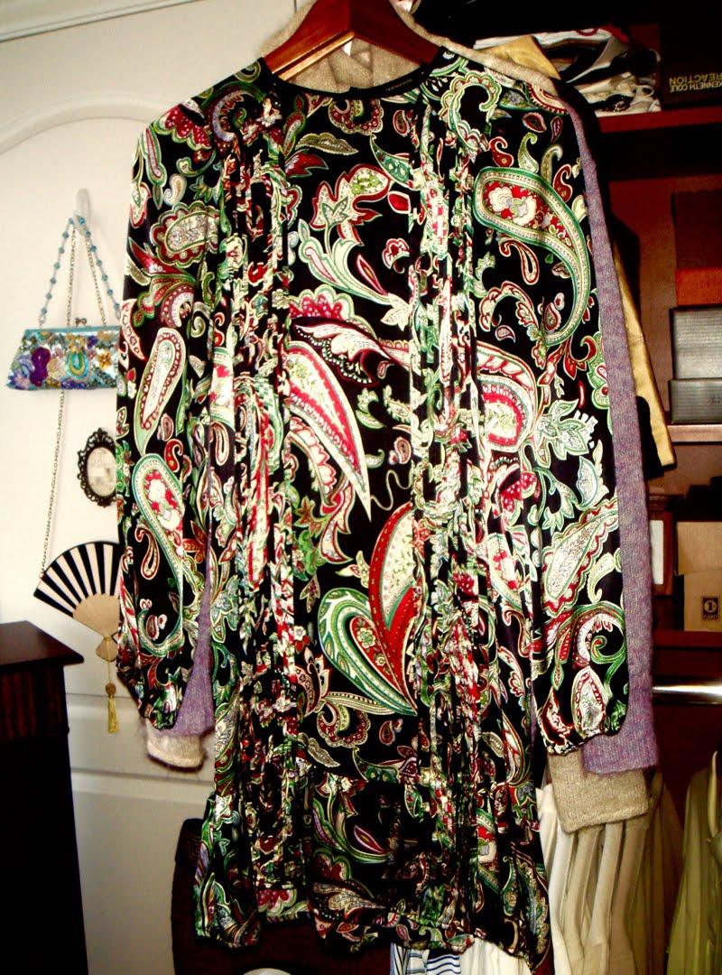 Black long sleeve printed paisley dress hanging up.
