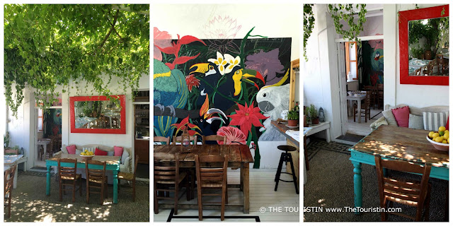 Bohemian style decorated courtyard restaurant with brightly coloured wall mural and massive mirror over a wooden sofa, overgrown by wine.