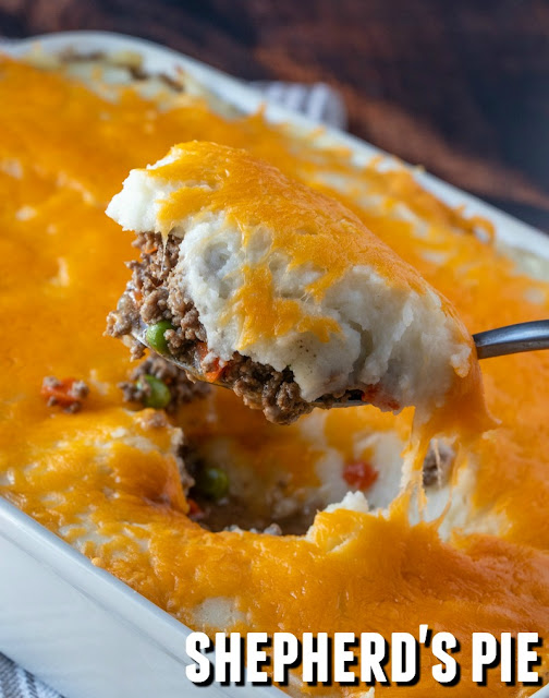 Cheesy mashed potato topped beef casserole with peas and carrots in a white casserole dish on a spoon