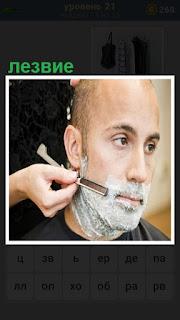 мужчину бреют лезвием бритвы парикмахер
