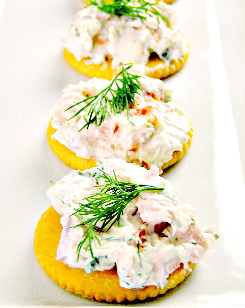 Smoked salmon appetizer bites on a white serving platter.