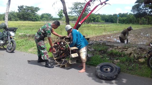 Babinsa Serda Suparman membantu memasang roda traktor guna mengolah lahan