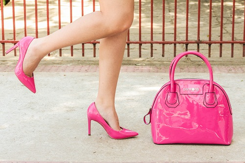 Mulher combinando bolsa feminina e sapato de salto alto rosa pink com verniz.