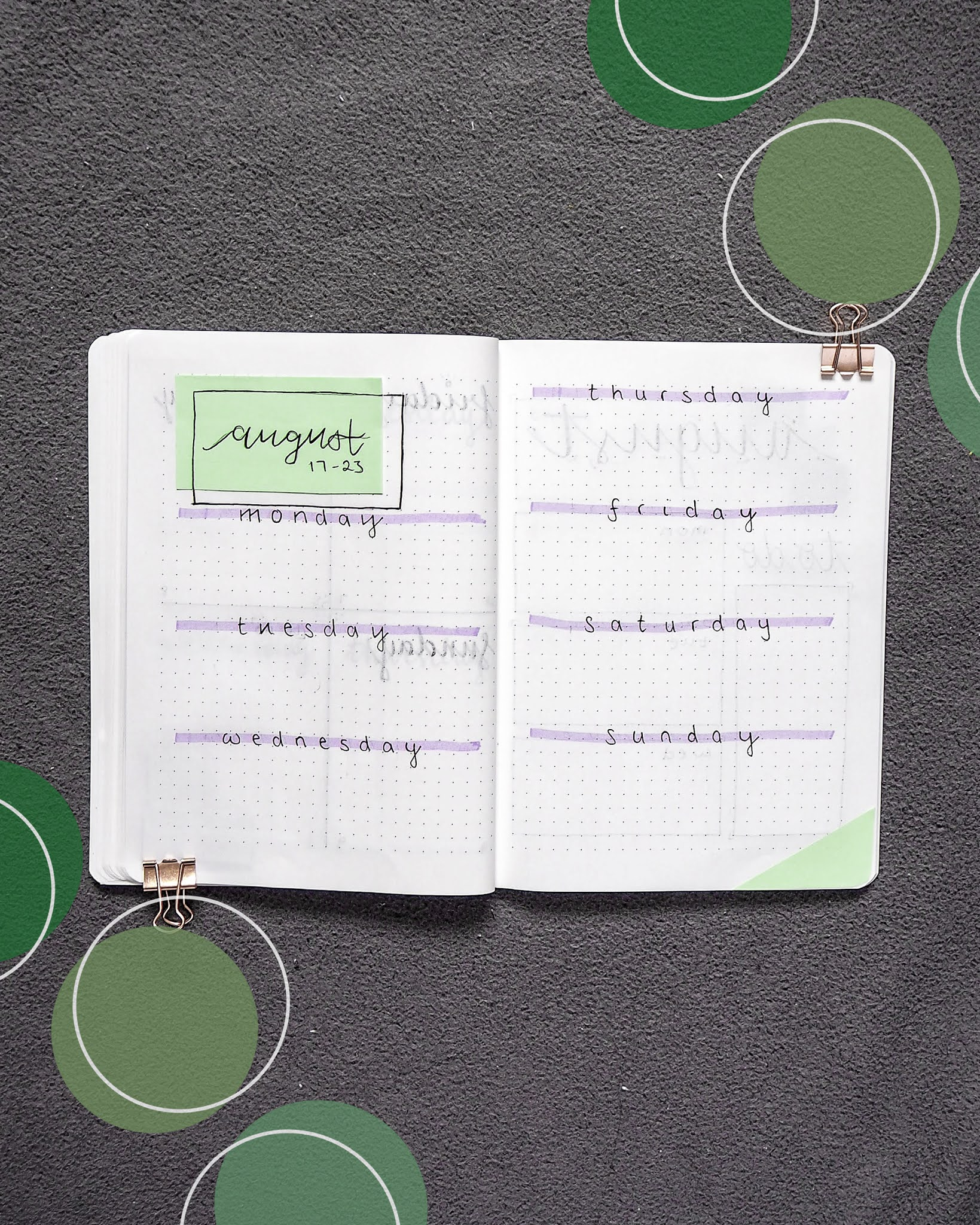 a green and purple themed bullet journal weekly spread. at the top of the first page is the month and days for the week (ie. 17-23). the rest of the two pages are split up into days with the divides going horizontal
