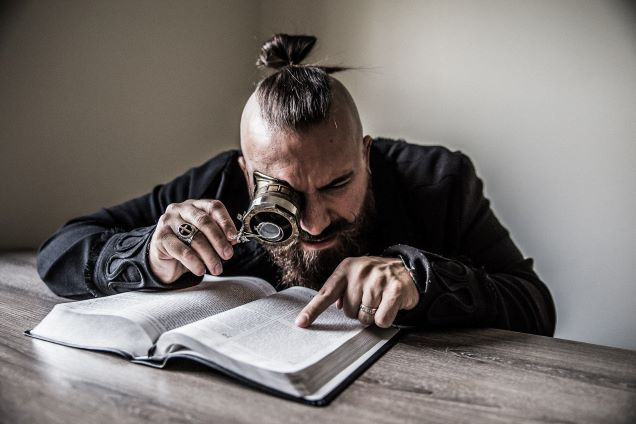 man using magnifying glass to study scripture