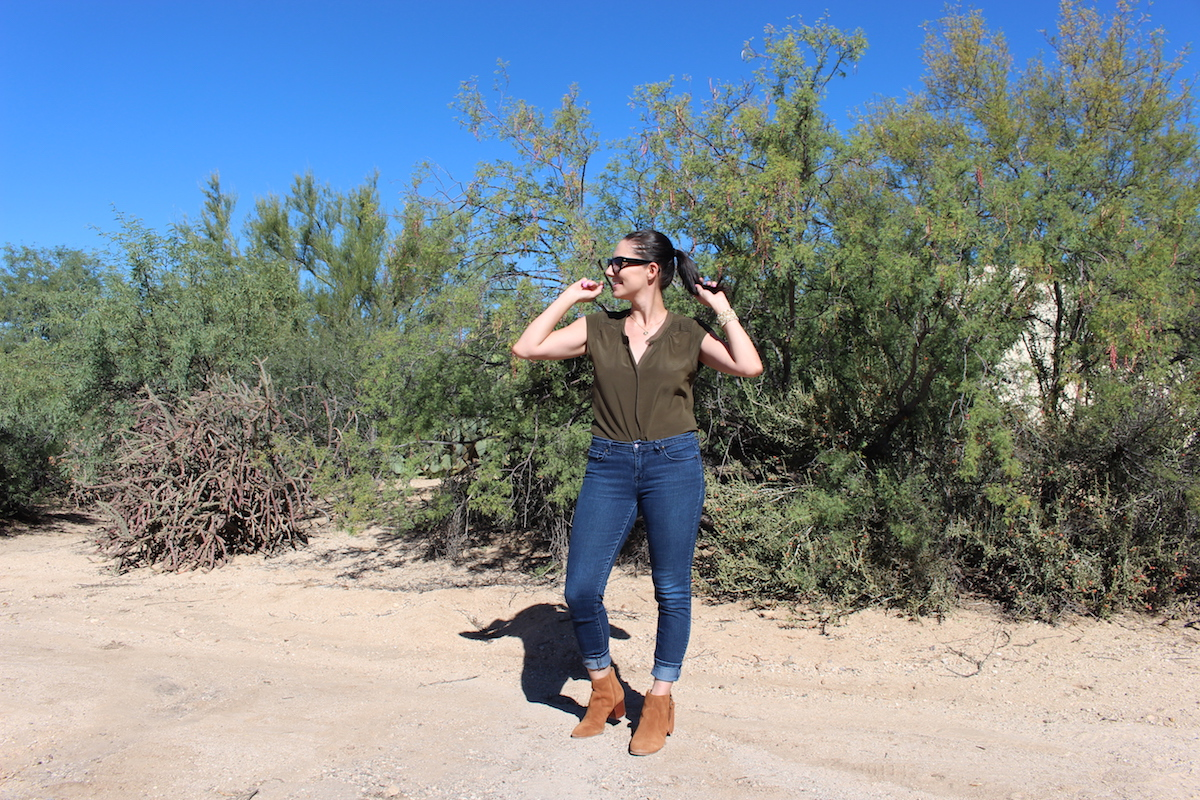 In this photo of me wearing jeans, a silk blouse, heels booties and cat-eye sunglasses, I am looking to the right with my left hand twirled around my ponytail and my right hand in the air.