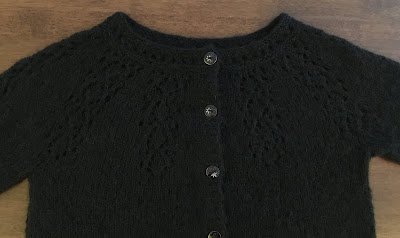 Black hand-knitted Nineveh cardigan showing lacy yoke