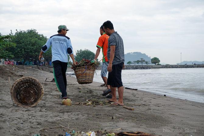 Petugas pantai membersihkan sampah dari laut