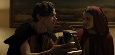 Bird, played by Kathryn Prescott, and Connor, played by Tyler Young, hold a Polaroid camera at a Halloween costume party in the movie Polaroid