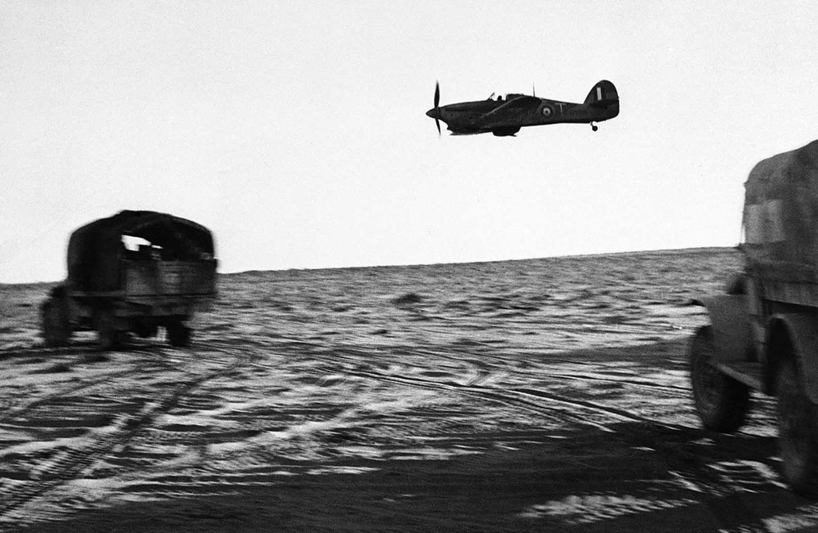 A low-flying Royal Air Force plane escorts rolling trucks of a New Zealand unit on the move in Egypt on August 3, 1942.