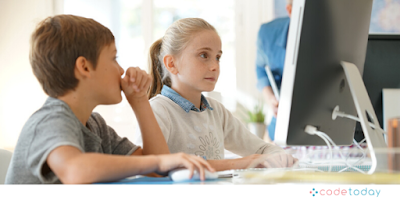 Boy and girl smiling and looking interested using a computer