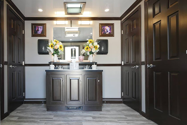 Large vanities that contain double porcelain sinks are on each side of the restroom trailer.