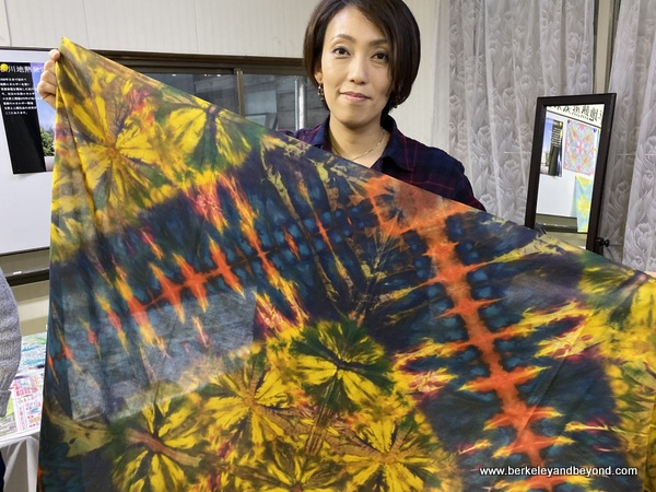 instructor holds sample tie-died cloth at Geocolor:  Hachimantai Geothermal Dyeing in Hachimantai city, Japan