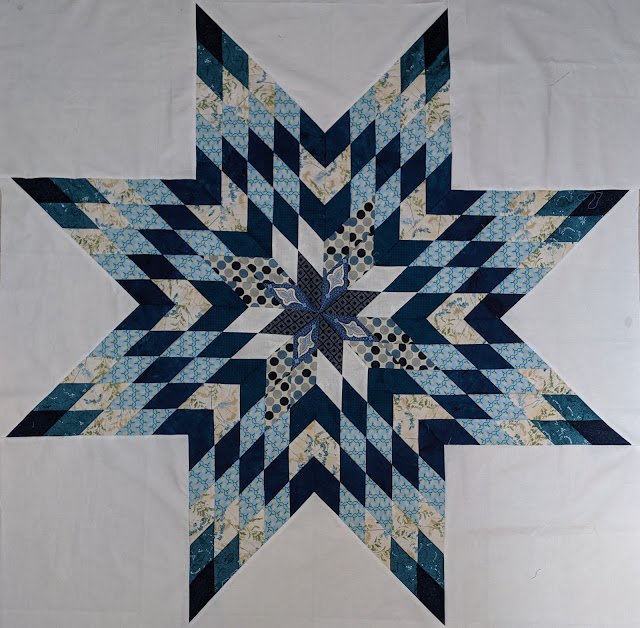 A full range of blue prints create a Lone Star on a solid white cotton background.