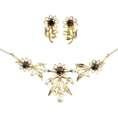 A gold necklace and earrings featuring gold flowers with garnets in the centre of each one