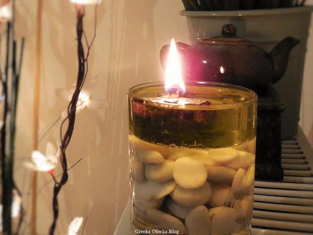 szklanka z płonącym płomieniem wypełniona wodą, oliwą, morskimi kamieniami