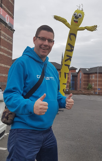 A wacky waving inflatable arm flailing tube man advertising Albion Mill Carpets in Ashton-under-Lyne