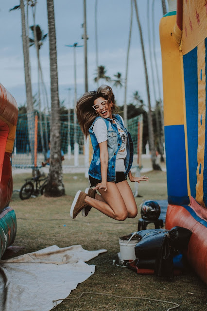 A girl mid-way jumping between two inflated jumping castles.