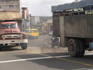 Kuba, Santiago de Cuba, stark befahrene Ausfallstraße, zwei Camiones, Motorräder, Taxi-Kleinbus, deutlich erkennbar die Abgasschwaden.