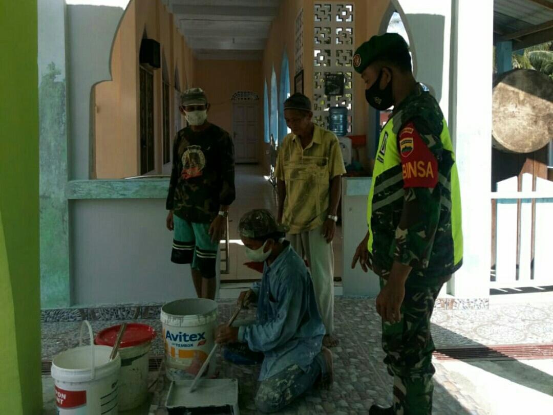 Babinsa Agung Sucianto Lakukan Komsos Dengan Warga Desa Sepempang Yang Sedang Mengecat Dinding Masjid Al Kautsar