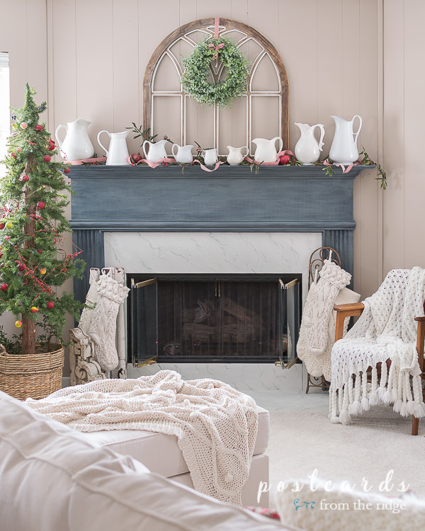 blue mantel with white ironstone pitchers and arched wooden church window frame