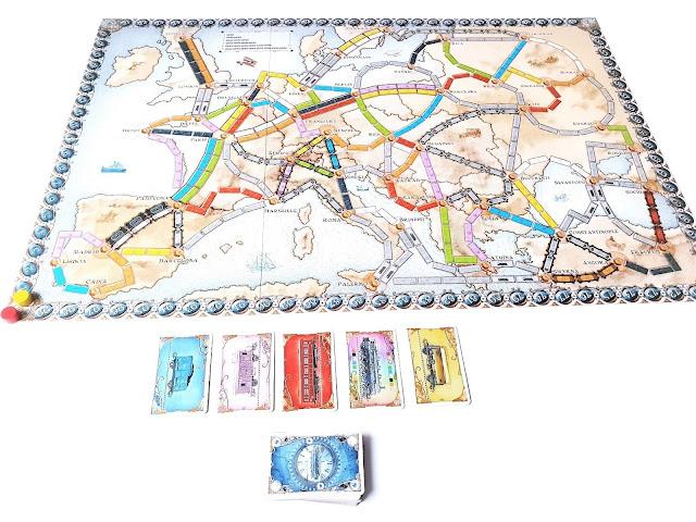 na zdjęciu plansza do gry  obok odkryte wagony do dobierania i zakryty stos kart z wagonami