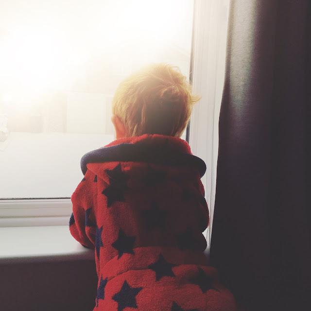 Little boy wearing a dressing gown looking out of the window to a snowy street