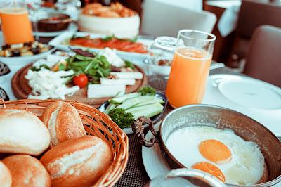 صورة لفطور صباحي فيها وجبات مختلفة من بيض مقلبي وخبر وسلطات وعصير برتقال وبعض الوجبات الاخرى