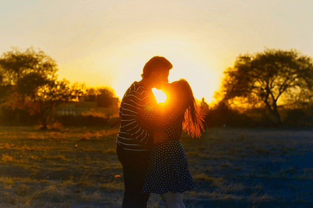 adult couples kissing sunset