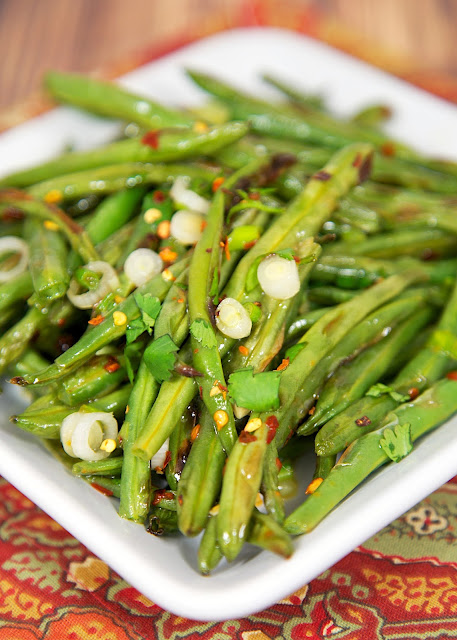 Fiery Green Beans - Ready in 15 minutes! Super easy weeknight side dish! Baked green beans tossed in lemon juice, cilantro, red pepper flakes and green onions. Tastes great warm or chilled. They actually taste better the longer they sit. SO good! Everyone gobbled these up!
