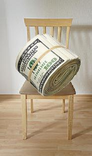 dollar-bill-stacks-on-chair-rolled-in-string