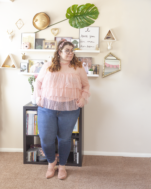 An outfit consisting of a pastel pink with pastel pink dots three layered bloue with sheer sleeves and blue highwaist jeans and muted pink pointed toe mules.