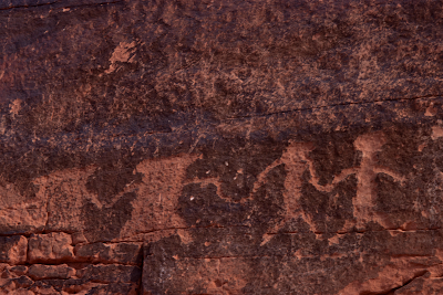 A photo of a petroglyph of two pairs of figures.